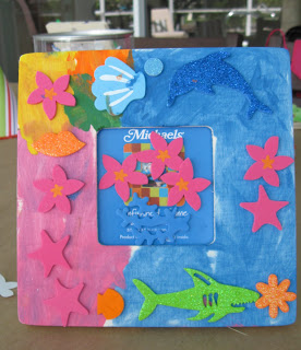Kids decorated frames with beachy accessories to go with the crafty birthday pool party theme.