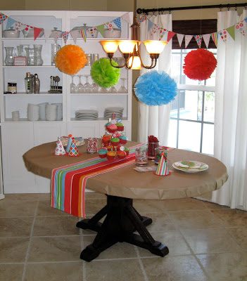 Homemade banners and pompoms look colorful and cheery above the birthday table.