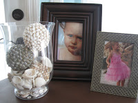 Family photos make the bedroom feel personal along with clear vases of seashells.