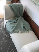 A chenille throw draped over a bench at the end of the bed.