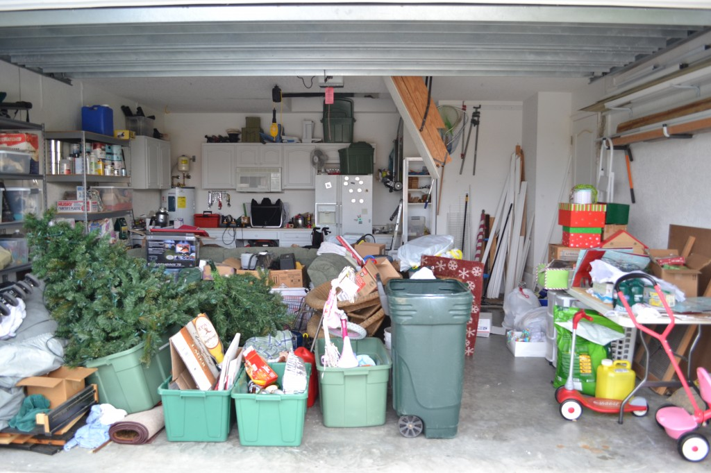 A cluttered garage full of stuff from Christmas decorations to bins and garbage cans.