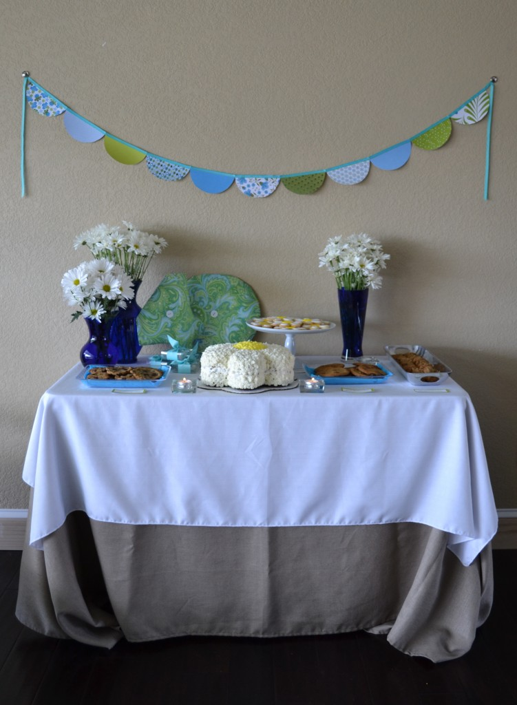 The DIY paper party garland above the dessert table is colorful.