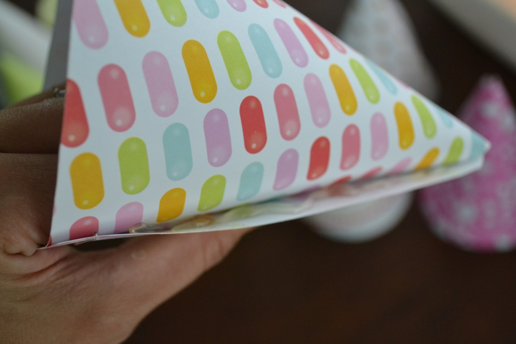 Once the scrapbook paper is cut, roll it into a cone-shaped hat.