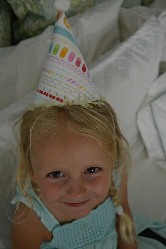 Looking darling in her cute diy paper party hat.