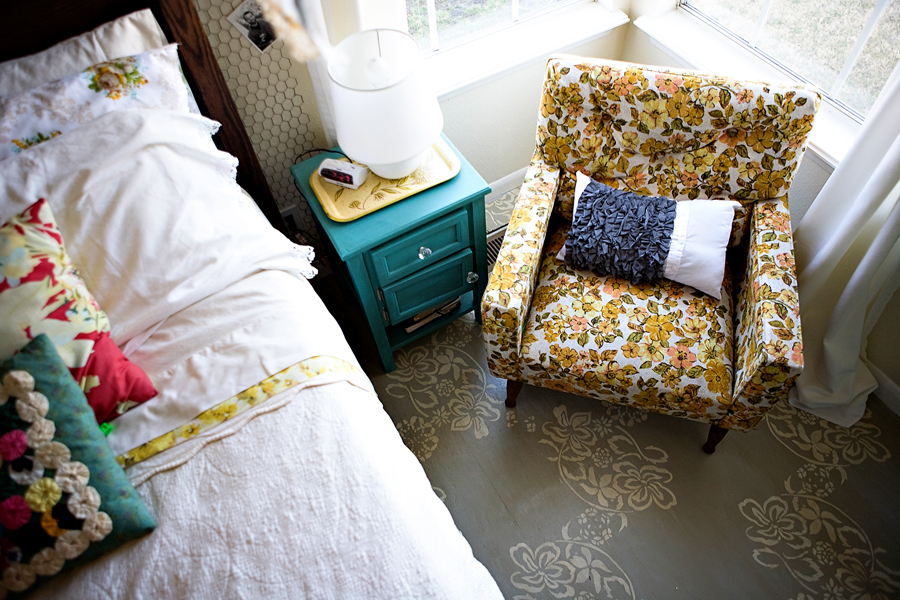 A coat of paint can update any piece, like this bright turquoise nightstand that looks fantastic in this boho style bedroom with vintage chair and pillows.