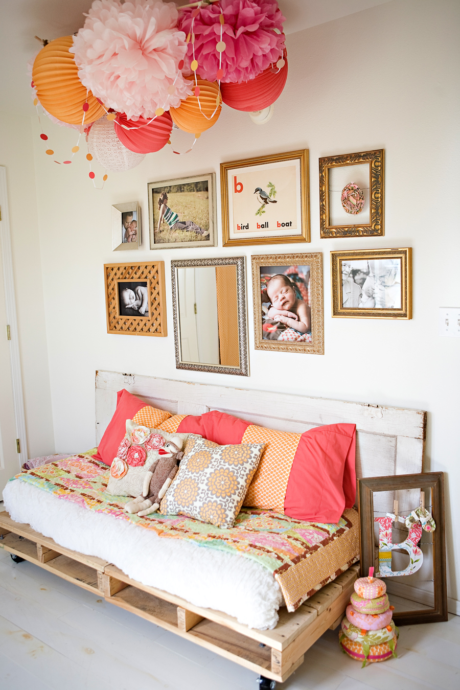 Simple items like inexpensive paper lanterns, garland and even reclaimed pallets and a door look fun, bohemian and eclectic under a gallery wall of fun frames.