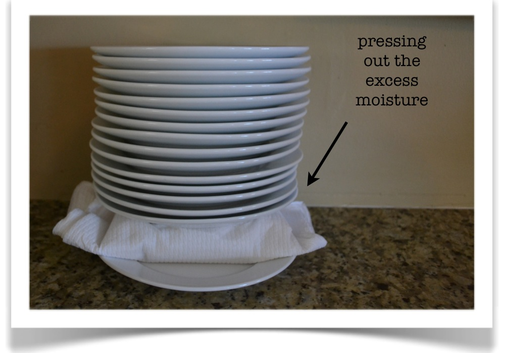 Pressing the wrapped tofu with a pile of plates will get rid of excess moisture.