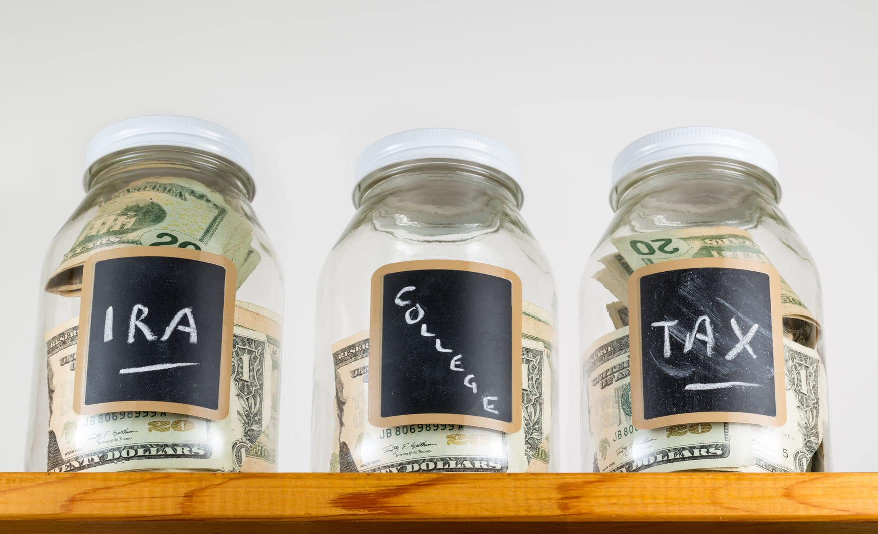 Different mason jars with cash labeled, IRA, College and Tax.