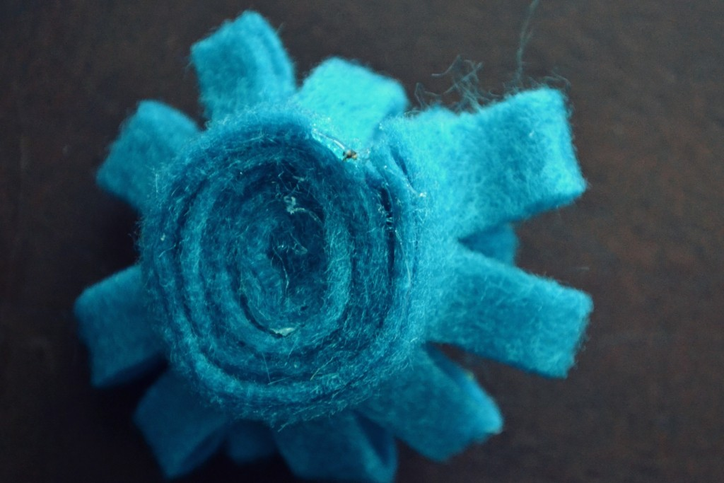 Roll flower tightly and glue in place with glue gun.