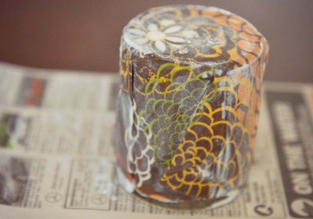 The next step in making an easy DIY Fabric-Covered Candle is to fold the fabric around the jar.