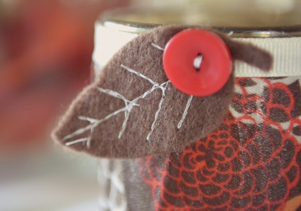 Add ribbon and the accent piece to the jar of your easy DIY Fabric-Covered Candle!