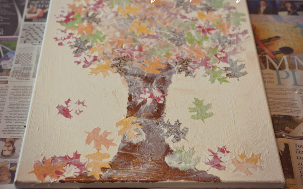 After placing all the leaves, cover the canvas in mod podge to seal in the paint and leaves