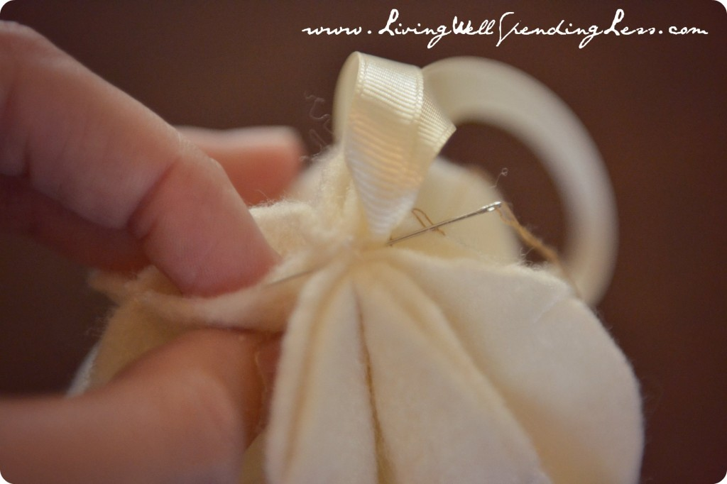 Using a needle and thread, stitch a loop of ribbon to the top of ornament.