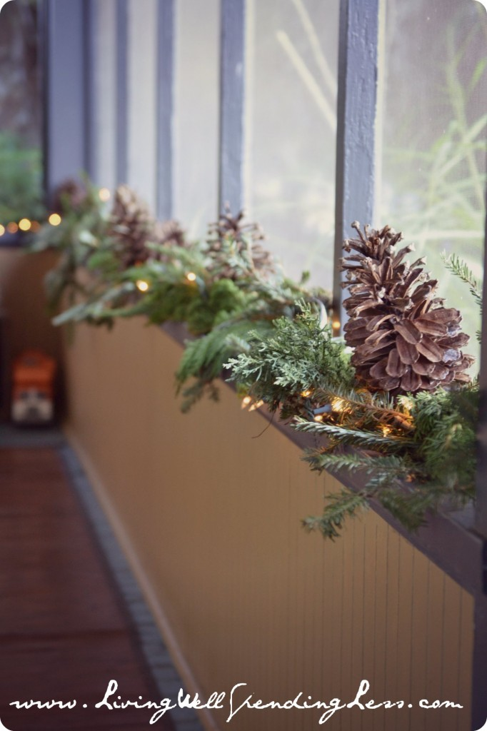 The pine cones, garland, and twinkle lights across the window ledge are a festive decor element.