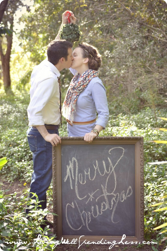 This happy couple shares a kiss under some mistletoe holding a Christmas sign.