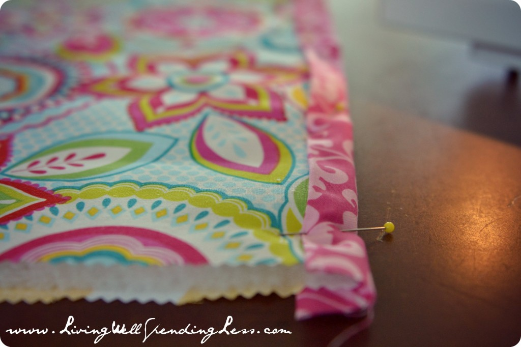 Pin the contrasting fabric edge to hold the top and bottom of the doll quilt together.