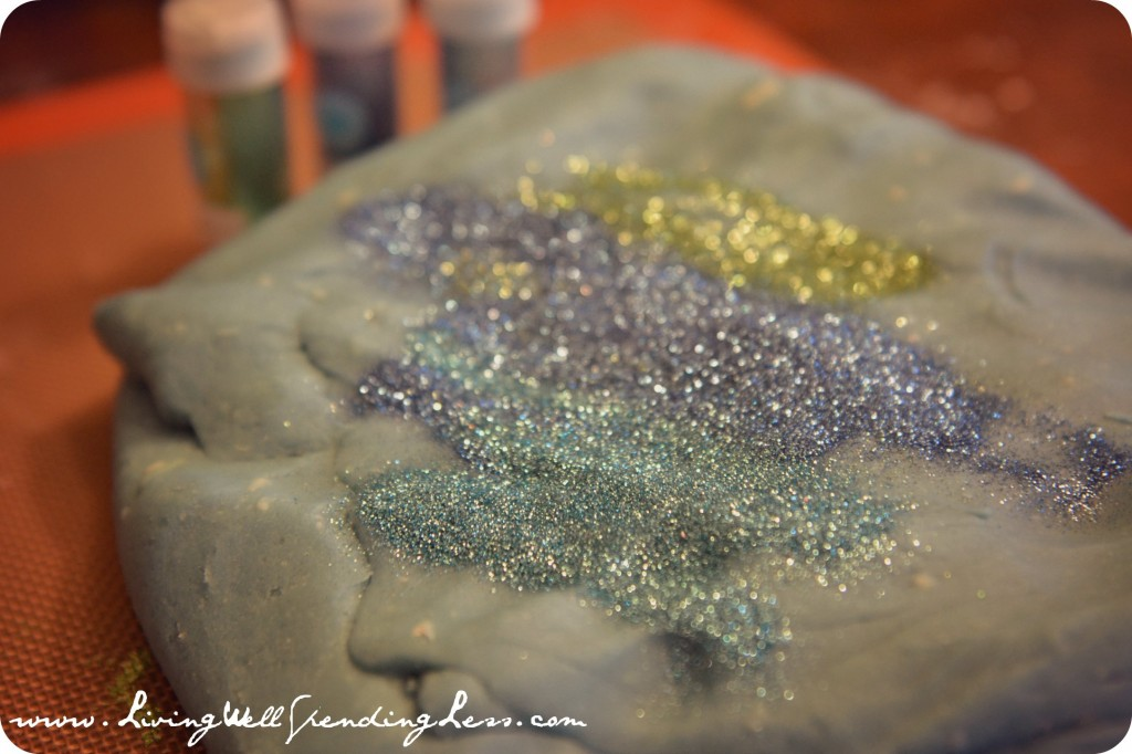 Sprinkle glitter on the playdoh lump and need together. Careful - this step can get messy!