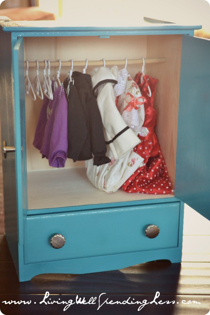 A pretty doll armoire with small clothes hanging in it.
