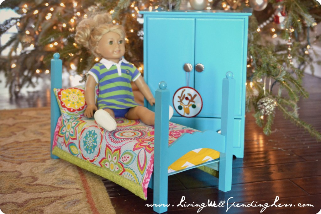 An American Girl doll sitting on a doll bed next to an armoire.