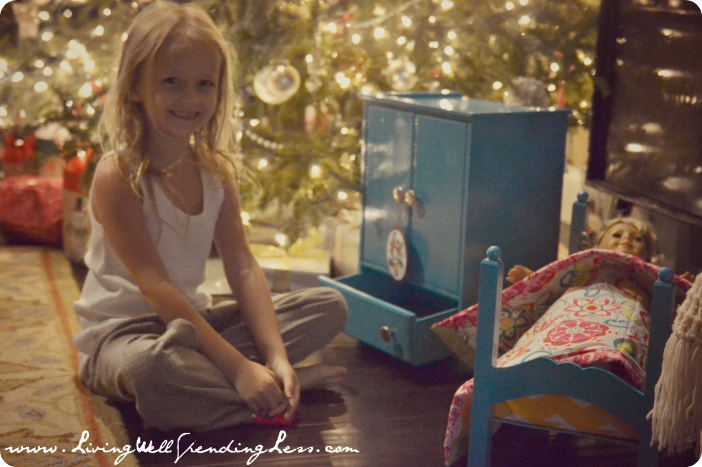 A content girl smiling next to her finished doll armoire next to the Christmas tree.