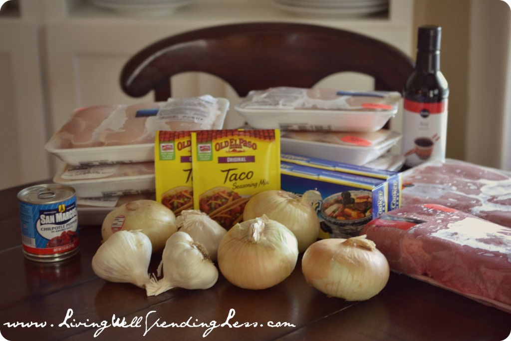 Assemble your various ingredients to begin freezer cooking meal prep: onions, garlic, meat, and more.