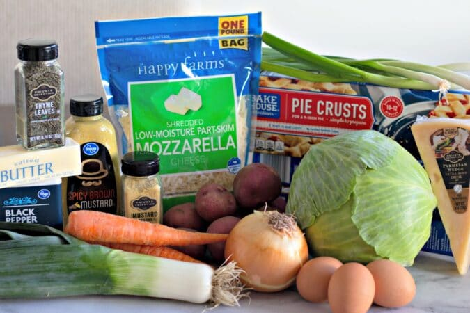 Assemble your ingredients, butter, eggs, potatoes, onions, carrots, green onion, cheese, pie crust, salt, pepper, mustard and cabbage