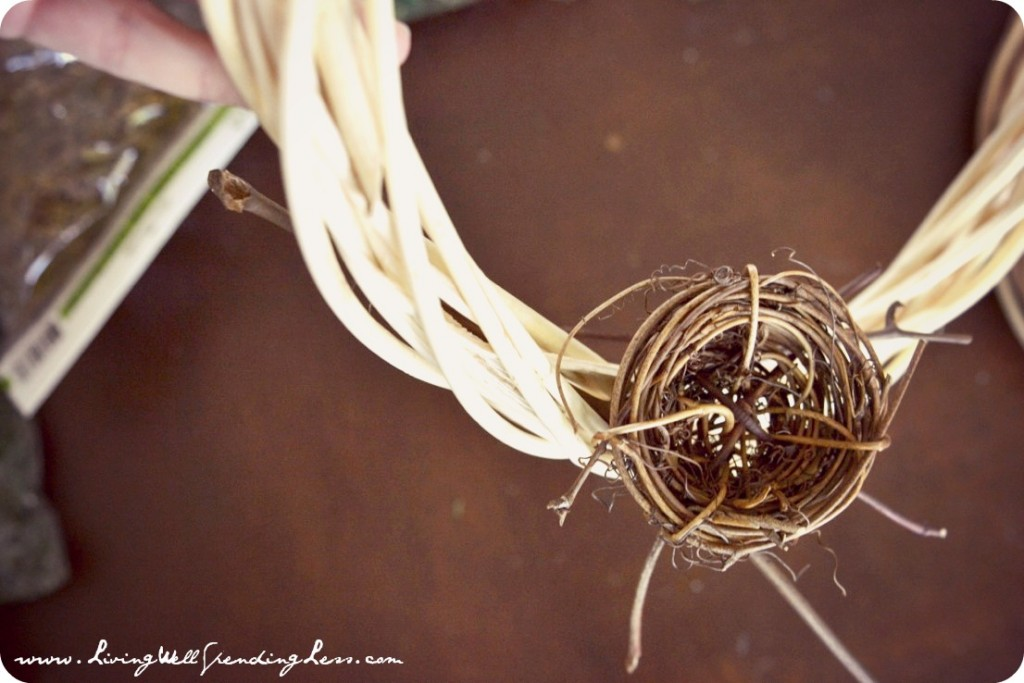 Twist the long stem of the decorative bird nest into the vines of the wreath.