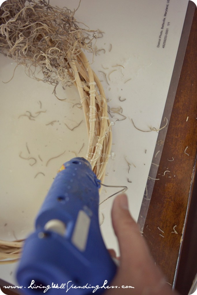 Spread hot glue over a section of the wreath then secure Spanish moss to wreath.