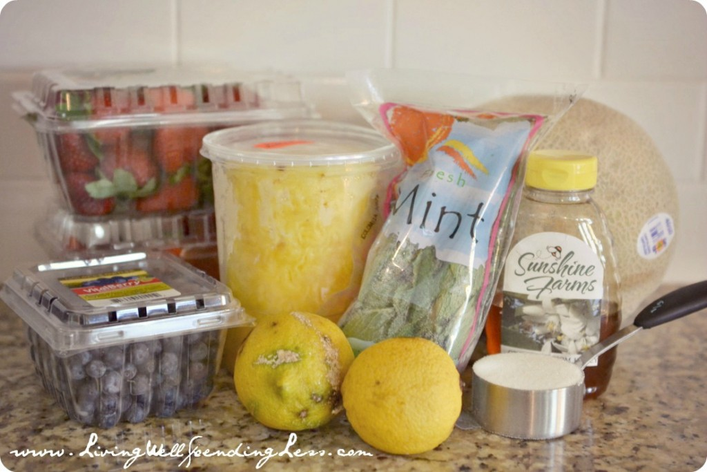 Assemble your fruit salad ingredients: fresh fruit, mint, sugar, water, honey and lemons.