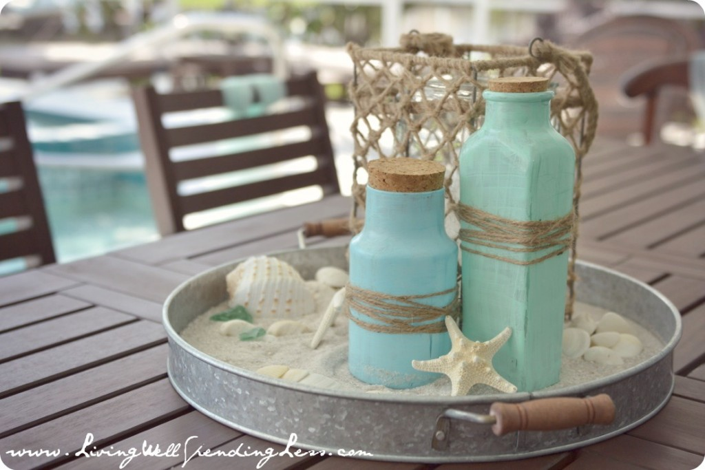 "Table centerpieces were made of sand, ""sea glass"" painted jars, shells and twine."