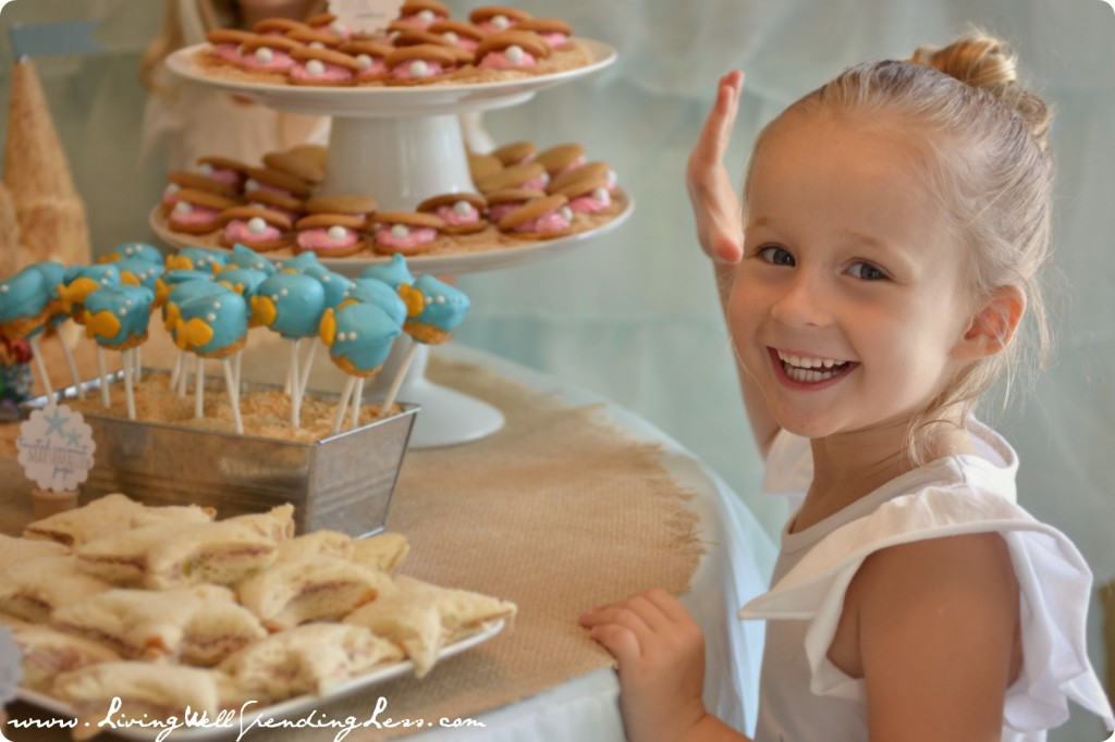 The birthday girl by the table of beach-themed party treats.