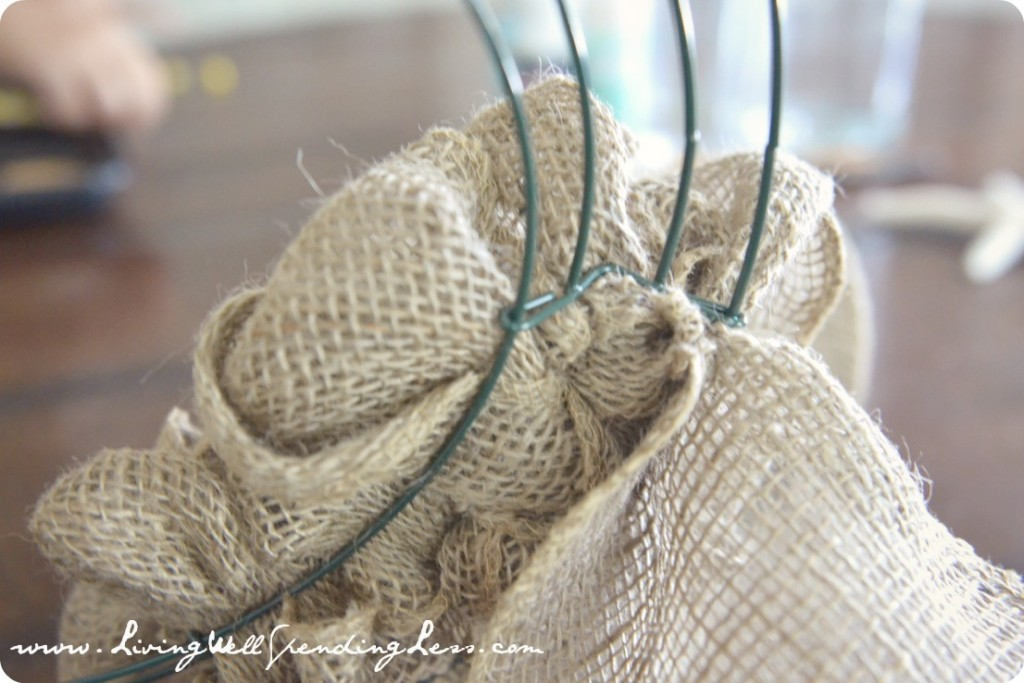 Wrap the burlap fabric all the way around the wreath frame.