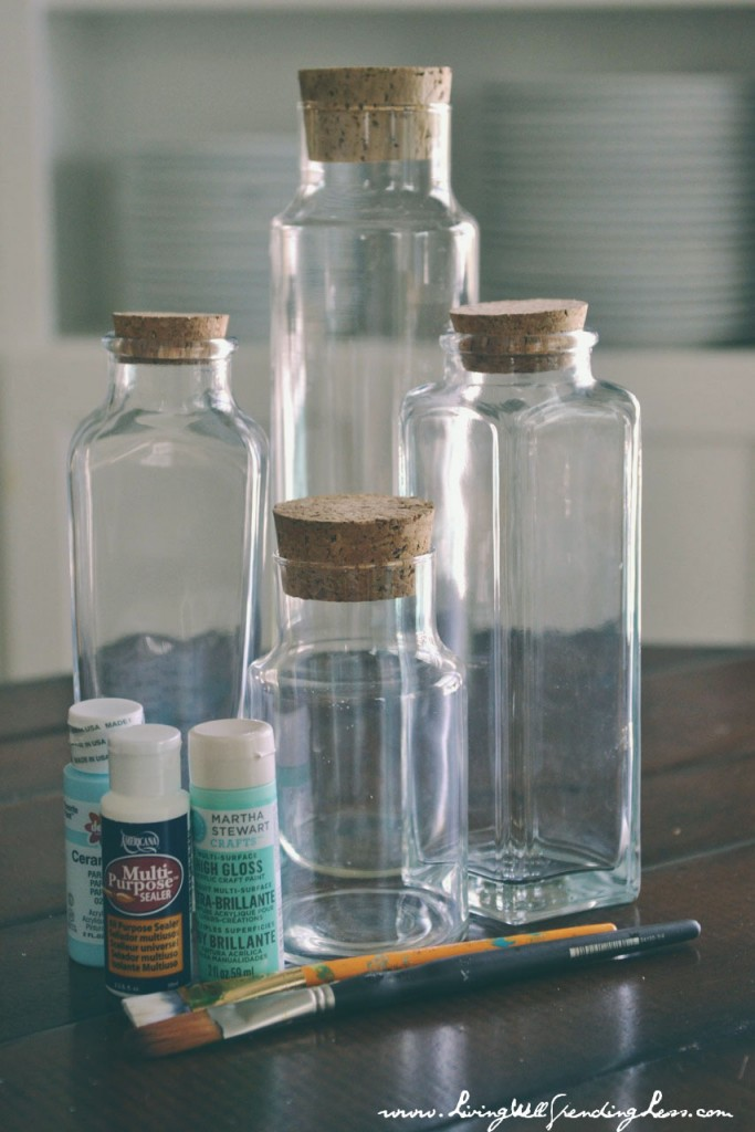 Assemble your materials: Glass bottles, sealer, paint brushes, and aqua or light blue acrylic paint.