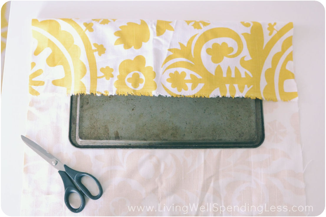 Cut a piece of fabric to wrap around cookie sheet.