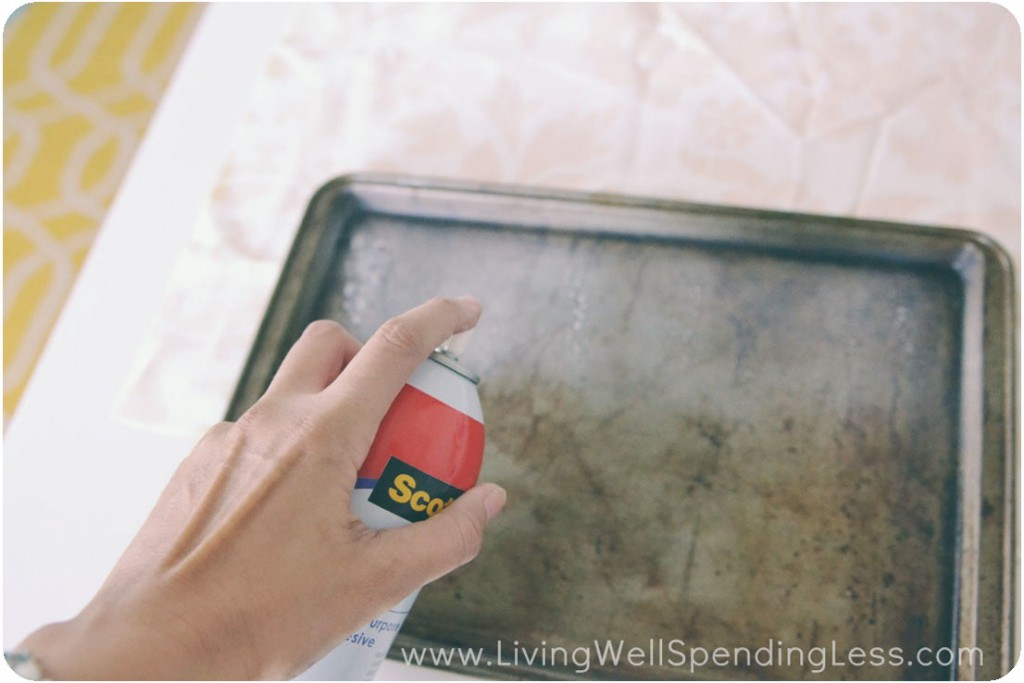 Spray the adhesive on the top and inner sides of the cookie sheet.