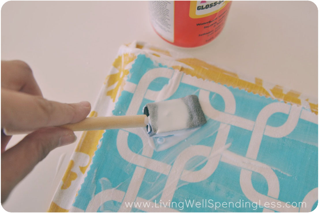 Brush the fabric on the back of the tray with Mod Podge.