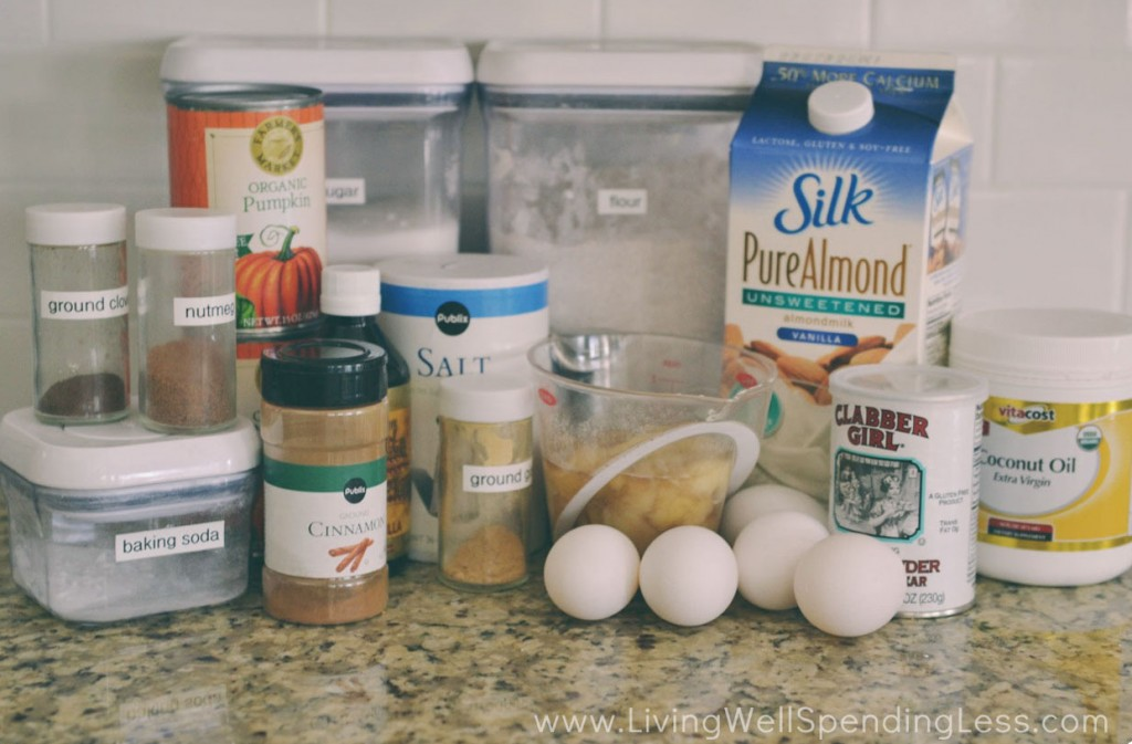 Assemble your ingredients for the skinny pumpkin bread: Whole wheat flour, baking soda, baking powder, salt, cinnamon, nutmeg, ground ginger, ground cloves, eggs, sugar, ripe bananas mashed, vanilla, coconut oil, unsweetened almond milk and pureed pumpkin.