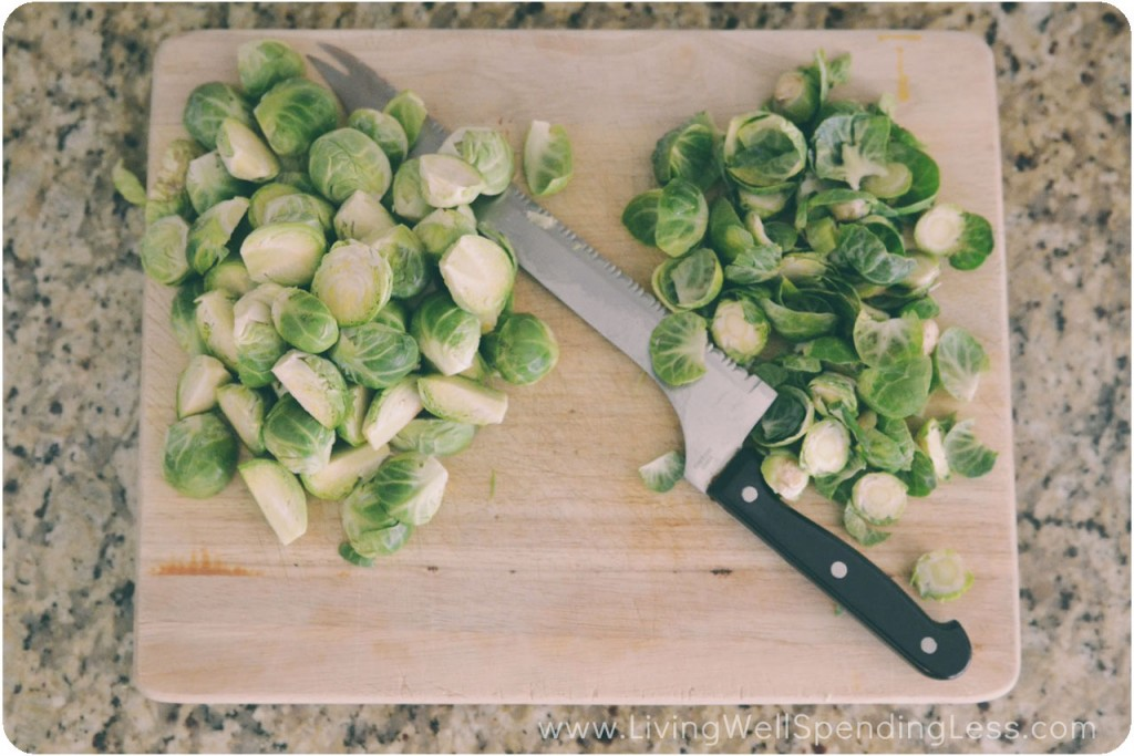 Chop Brussels sprouts on a cutting board with a knife.