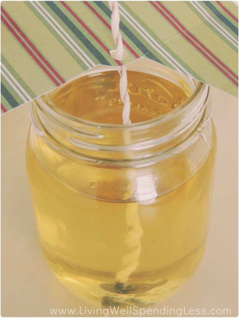 Pour the melted wax into your Mason jar, making sure the wick stays upright by using a piece of paper with a hole punched in it.