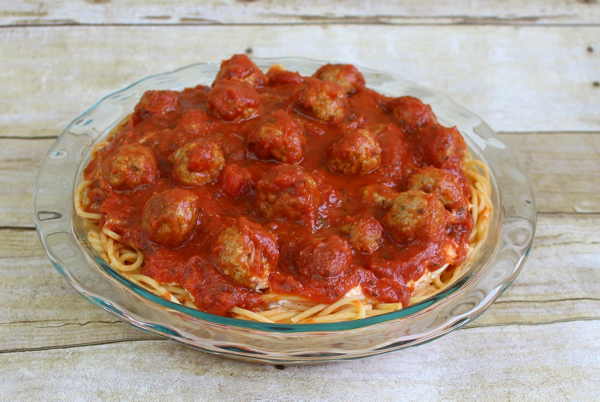 "Spread sauce and meatballs over ricotta and pasta ""crust."""
