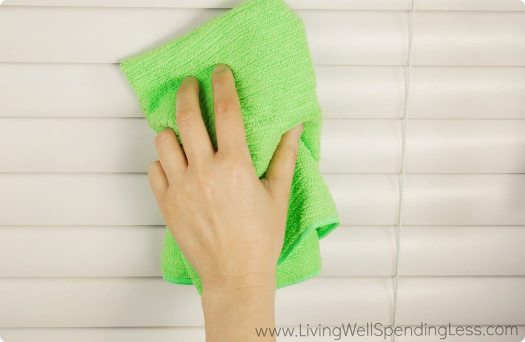 A person cleaning blinds with a towel.
