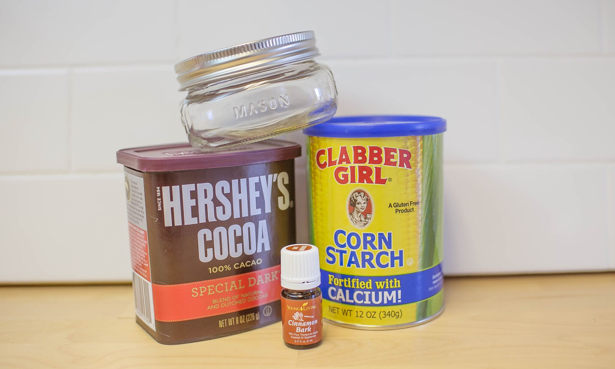 Assemble your materials to make DIY dry shampoo: Cocoa powder, essential oil, corn starch and a mason jar.