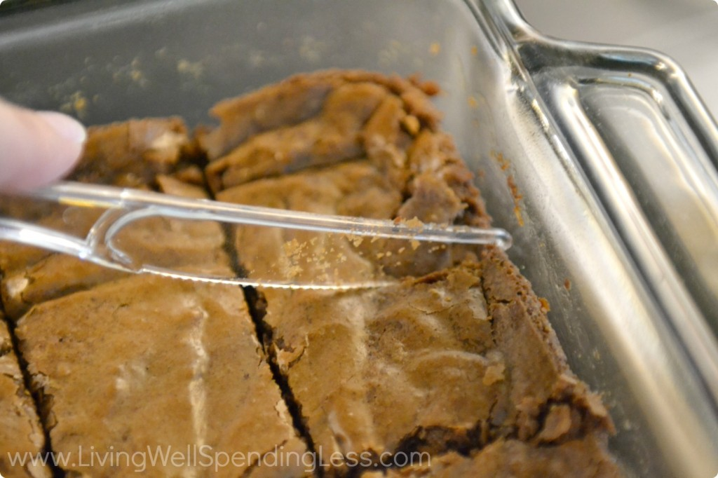 Cut baked brownies into 2x2 inch squares with plastic knife.
