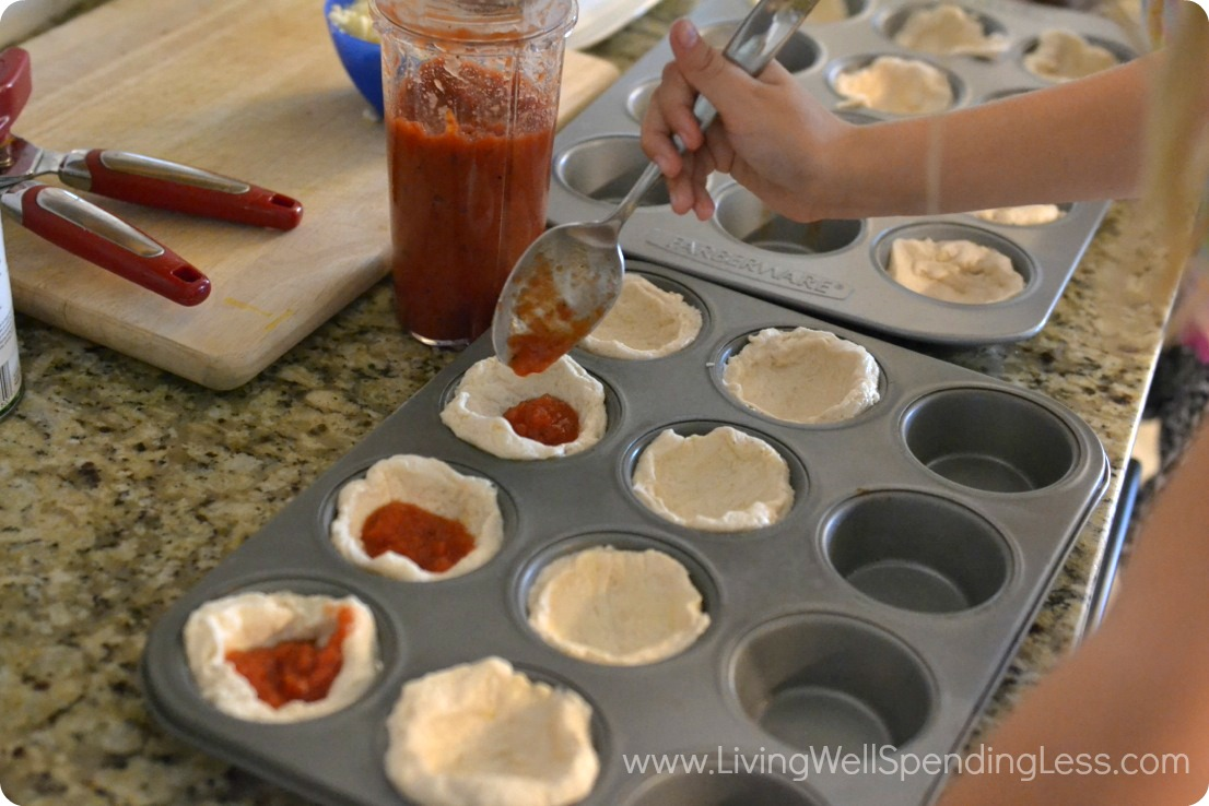 Spoon pizza sauce in biscuits