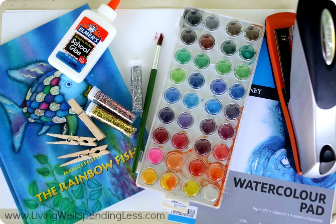 Assemble your materials to make your rainbow fish puppets: Card stock or watercolor paper, watercolor paints and brush, glue, glitter, scissors, clothes pins and the Rainbow Fish book.
