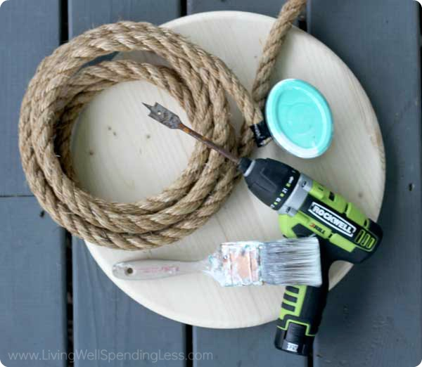 The supplies you need for your DIY tree swing - a long rope, paint, a sturdy wood circle, paint brush, and a drill with a spade bit.