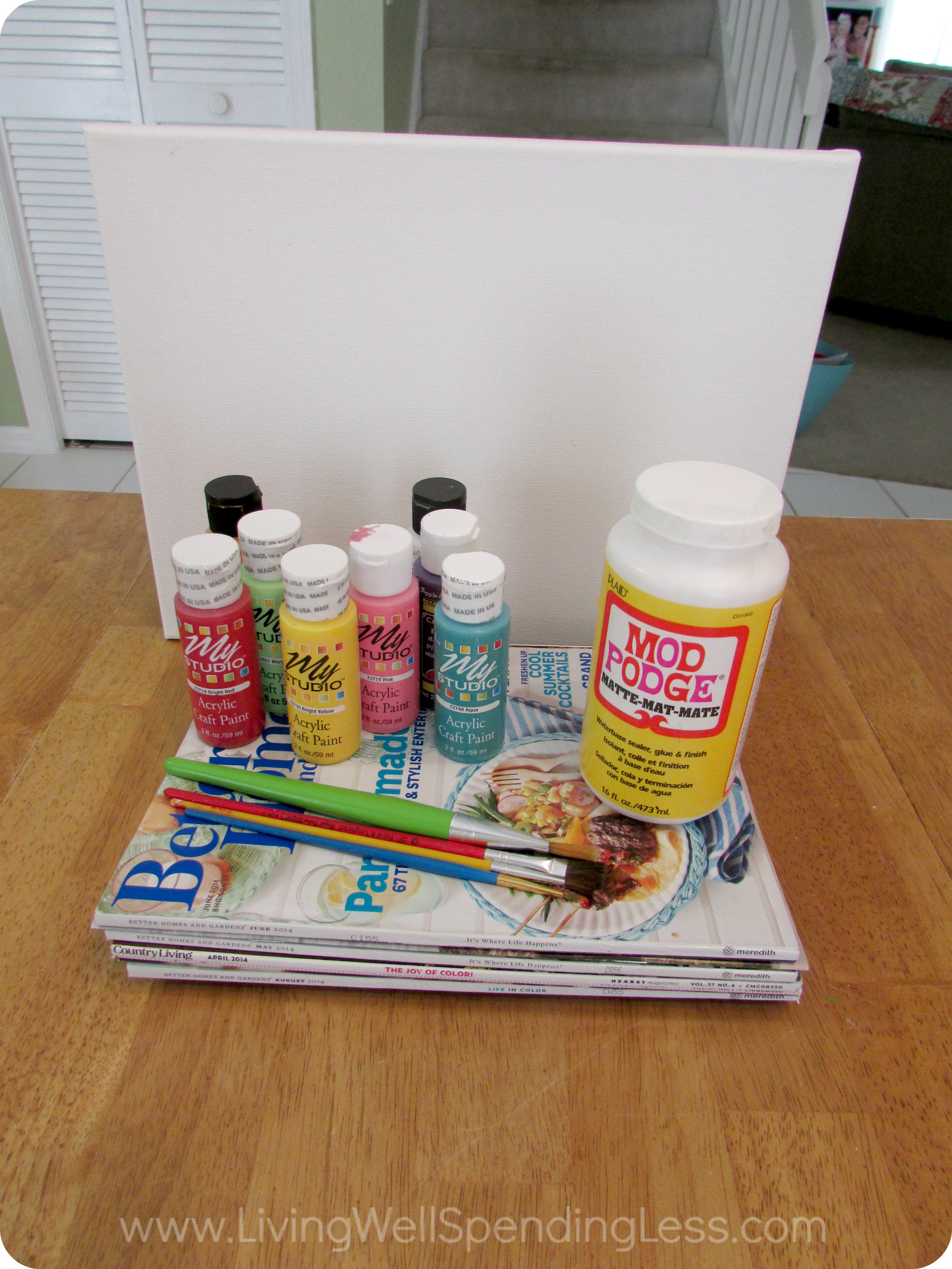 Gather all the necessary materials: Canvases, acrylic paints, paint brushes, old magazines, scissors and Mod Podge.
