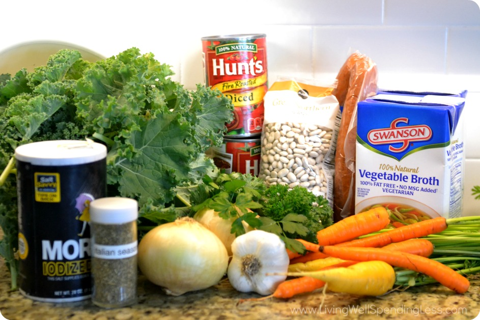 Gather the ingredients for this soup: kale, white beans, vegetable broth, onions, carrots, tomatoes and seasonings.