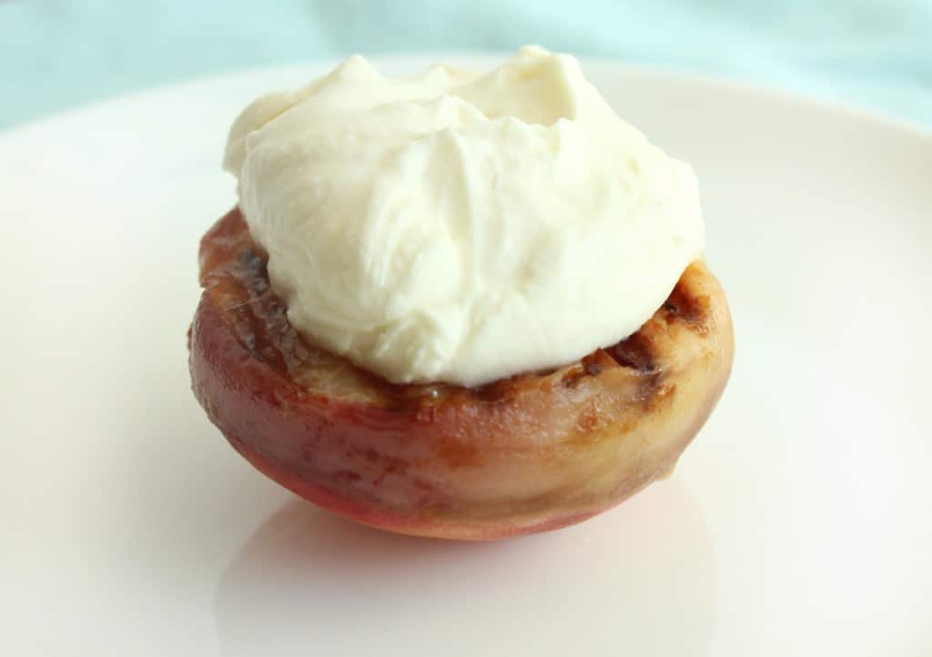 While the grilled peaches are still warm, add the whipped marscapone topping.