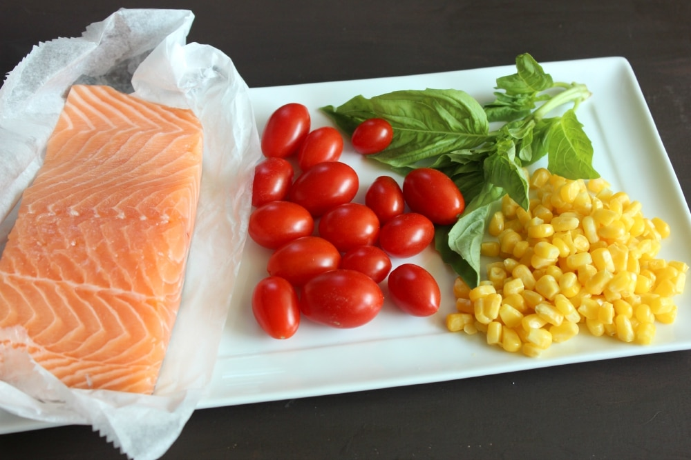 Assemble your ingredients: salmon, cherry tomatoes, basil, and corn.